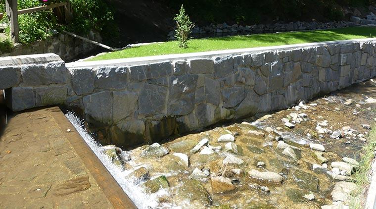 Granitmauer als Begrenzung eines Wasserlaufs